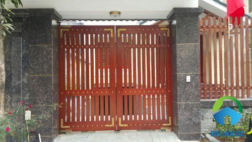 Gạch giả đá màu nâu đen tương phản với màu đỏ của cổng nhà